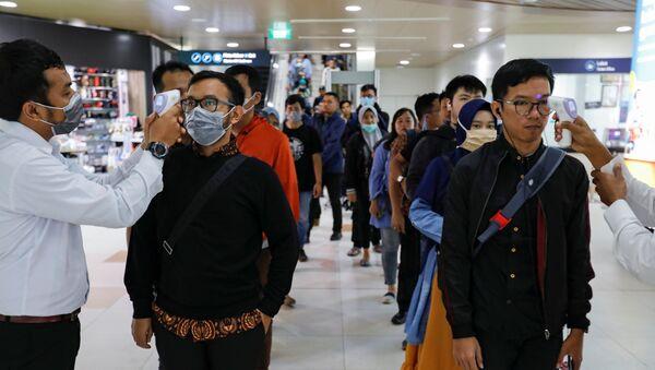 Los médicos miden la temperatura de los pasajeros debido al brote de coronavirus - Sputnik Mundo