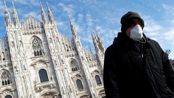 Un hombre con mascarilla en Milano - Sputnik Mundo