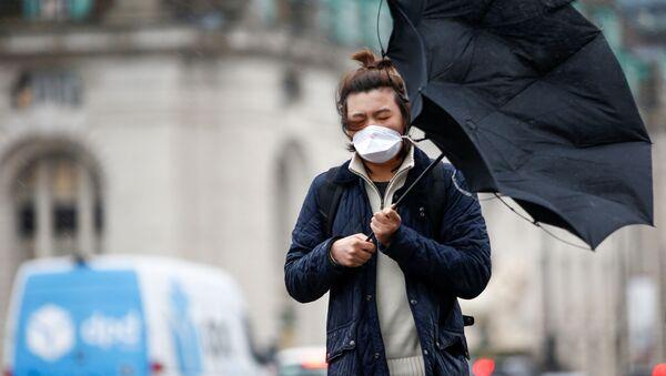 Un hombre con mascarilla en Londres - Sputnik Mundo