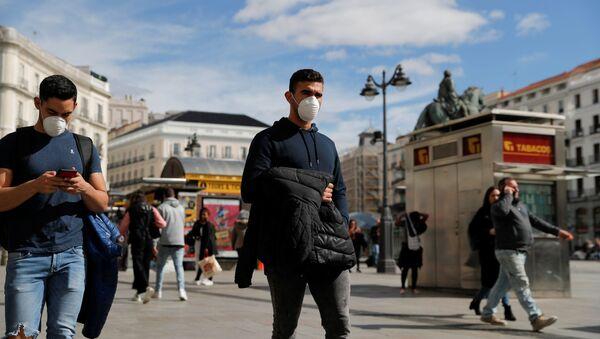 Unos hombres con mascarilla durante el brote del coronavirus en España - Sputnik Mundo