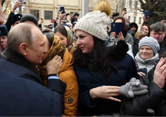 El presidente ruso, Vladímir Putin, y una mujer de la ciudad de Ivánovo
