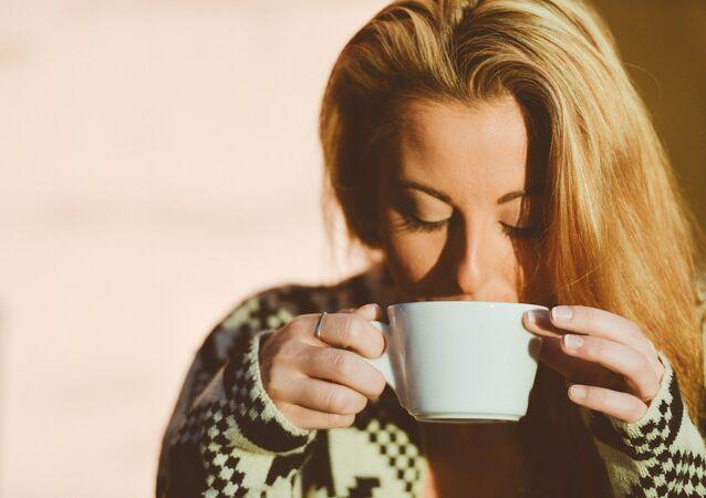 Una mujer toma café, referencial