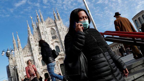 Una mujer lleva la mascarilla en Milán - Sputnik Mundo