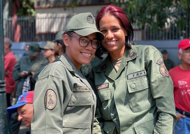 Dos mujeres militares venezolanas participando en la marcha por el Dia de la Mujer en la avenida Universidad de Caracas.