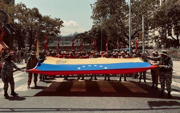 Milicianos y milicianas sosteniendo la bandera de Venezuela en la marcha por el Dia de la Mujer en Caracas. - Sputnik Mundo
