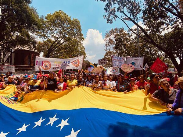 Un grupo de mujeres que participan en la multitudinaria marcha por el Dia de la Mujer en Caracas portan una bandera gigante de Venezuela mientras avanzan caminando por la avenida Universidad en direccion al Panteon Nacional, punto final de la manifestacion. Las mujeres van cantando consignas revolucionarias y en pro de los derechos de la mujer en el mundo. - Sputnik Mundo