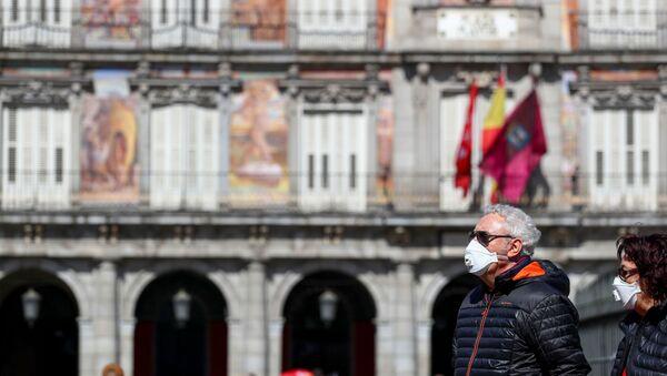 Dos personas con mascarillas en la Plaza Mayor de Madrid - Sputnik Mundo