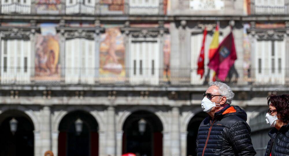 Dos personas con mascarillas en la Plaza Mayor de Madrid