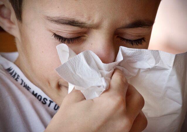 Un niño estornudando y con un pañuelo. Imagen referencial