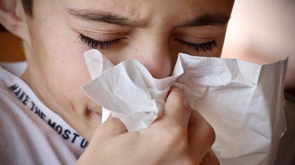 Un niño estornudando y con un pañuelo. Imagen referencial - Sputnik Mundo