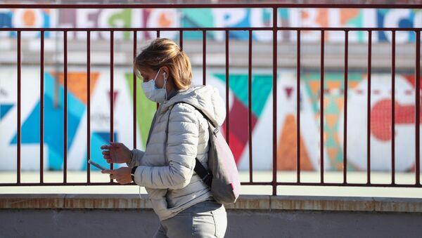 Una mujer con mascarilla en Madrid - Sputnik Mundo