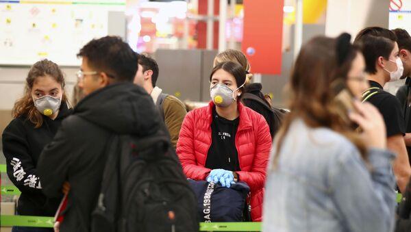 La gente con mascarillas durante el brote de coronavirus en Madrid, España - Sputnik Mundo