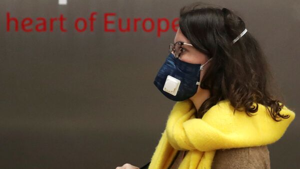 Una mujer con mascarillas en Bruselas - Sputnik Mundo