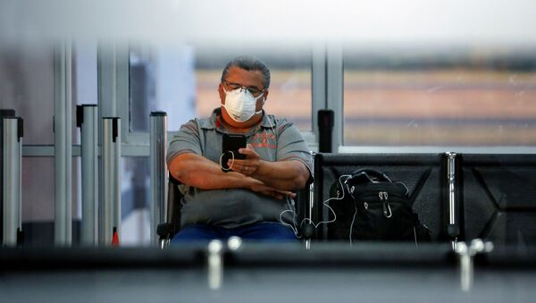 Un hombre con una mascarilla debido al coronavirus en el aeropuerto en El Salvador - Sputnik Mundo