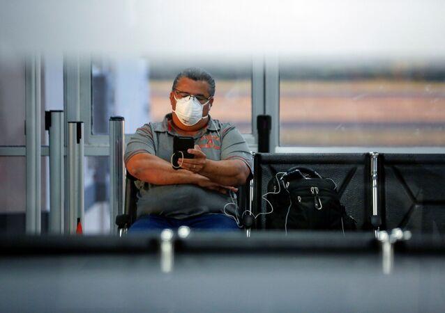 Un hombre con una mascarilla debido al coronavirus en el aeropuerto en El Salvador