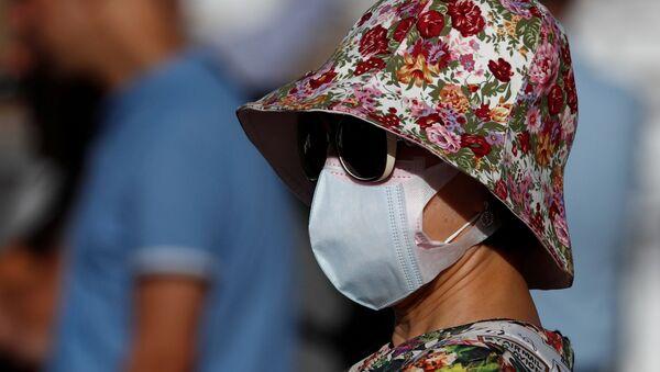 Una mujer lleva una mascarilla - Sputnik Mundo