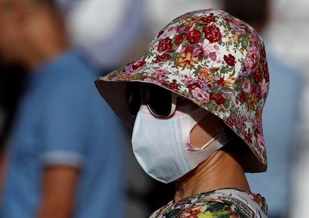 Una mujer lleva una mascarilla