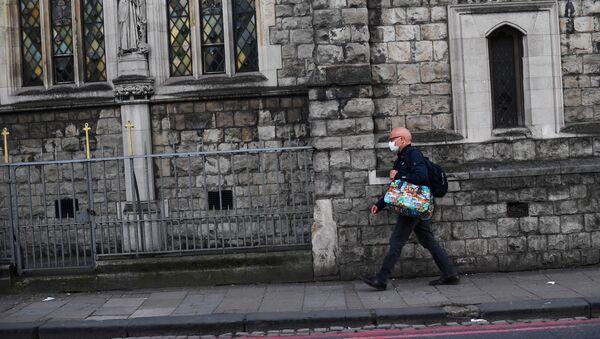 Un hombre en mascarillas en Londres - Sputnik Mundo