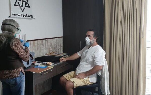 David Uzal en su habitación de hotel en Caracas mientras una doctora le realiza las pruebas para saber si tiene coronavirus - Sputnik Mundo