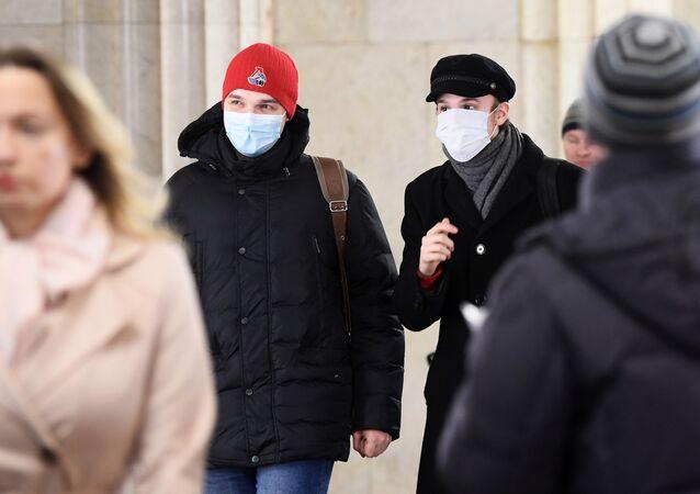 La gente en mascarillas en el metro de Moscú