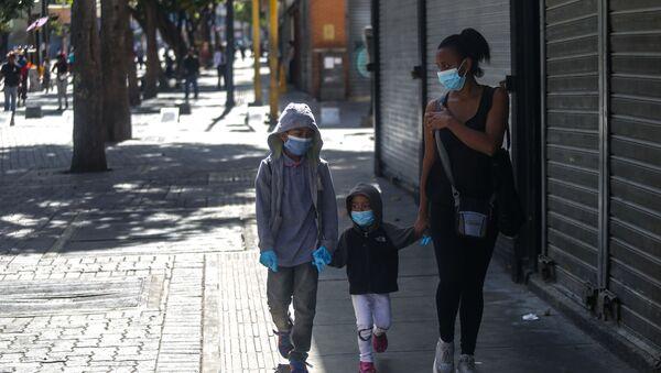 Niños con tapaboca caminando con una mujer - Sputnik Mundo