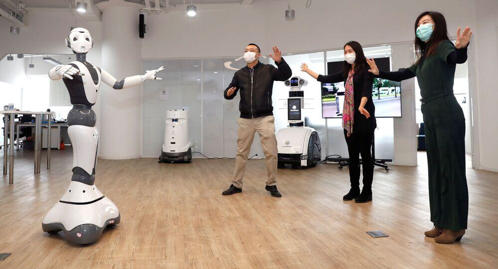 Los miembros del personal que llevan máscarillas gesticulan junto a un robot 5G con el fin de dar consejos médicos relacionados con coronavirus