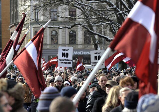 La gente con las banderas de Letonia para conmemorar a los veteranos de la Legión Letona del cuerpo armado de Waffen-SS