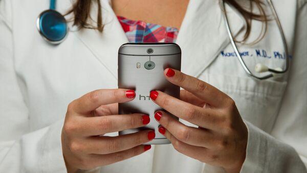 Una doctora con un móvil (imagen referencial) - Sputnik Mundo