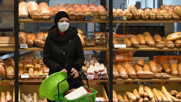 Una mujer con mascarilla en un supermercado en Moscú - Sputnik Mundo