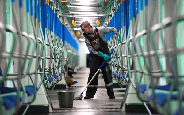 Un empleado frega el suelo en un tren del metro de Moscú - Sputnik Mundo