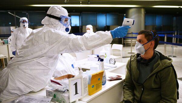 Un médico toma la temperatura a un pasajero en un aeropuerto de Rusia - Sputnik Mundo