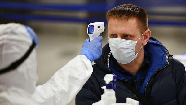 Un médico tomando la temperatura a un hombre con mascarilla durante brote de coronavirus en Moscú, Rusia - Sputnik Mundo