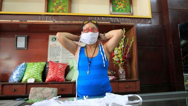 Una cubana se pone la mascarilla protectora - Sputnik Mundo