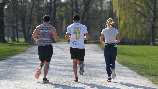 Tres personas corriendo en el Jardín Inglés de Múnich, Alemania - Sputnik Mundo