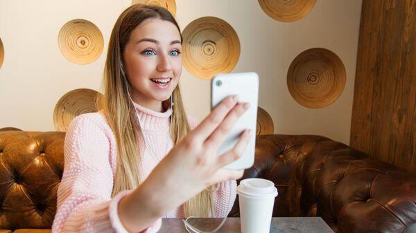 Una joven con un smartphone - Sputnik Mundo