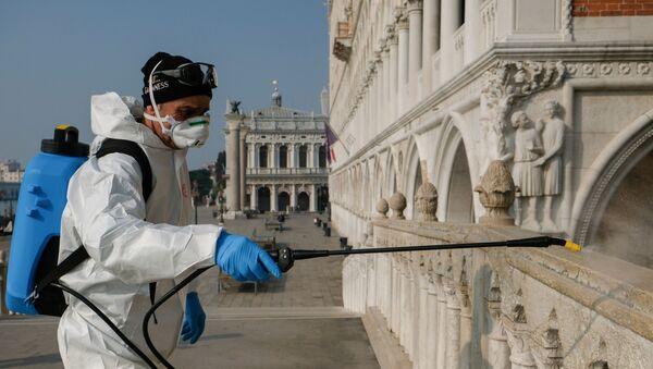 Un hombre desinfectando las calles de Venecia, Italia - Sputnik Mundo