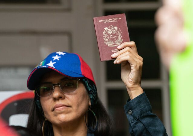 Una mujer sostiene en sus manos un pasaporte venezolano