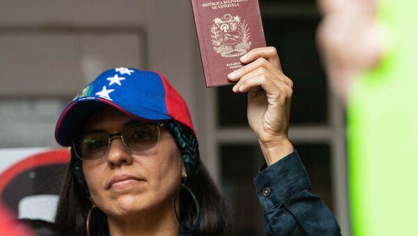 Una mujer sostiene en sus manos un pasaporte venezolano - Sputnik Mundo