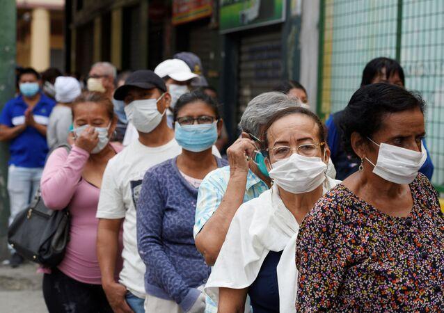Personas mayores con mascarillas haciendo cola en Ecuador
