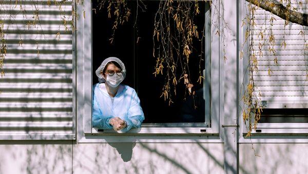 Una mujer con mascarilla - Sputnik Mundo