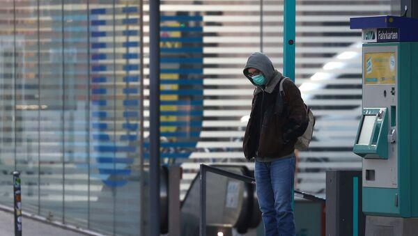 Un hombre con mascarilla en Alemania durante el brote del coronavirus - Sputnik Mundo