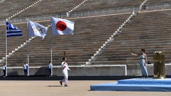 La ceremonia de entrega del fuego olímpico sin espectadores en las gradas - Sputnik Mundo