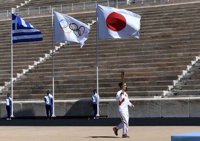 La ceremonia de entrega del fuego olímpico sin espectadores en las gradas