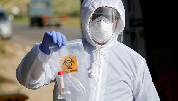 Un médico con un test de coronavirus - Sputnik Mundo