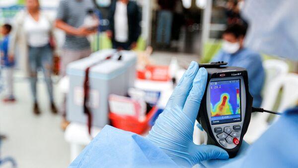 El personal médico con un escáner térmico en Ecuador - Sputnik Mundo
