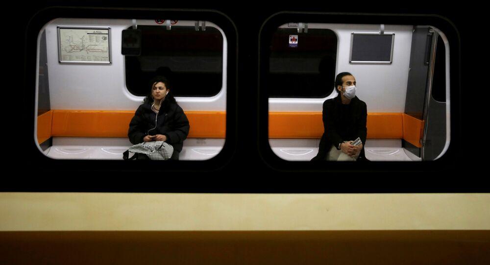 Dos personas mantienen la distancia en un tren por coronavirus