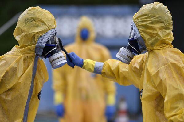 Personal médico vestido con trajes protectores reciben instrucciones sobre la pandemia del coronavirus en Brasil. - Sputnik Mundo