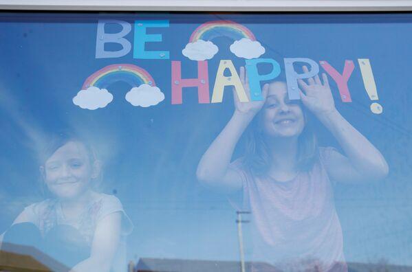 Niños mirando por la ventana de una casa en St. Helens, Reino Unido. - Sputnik Mundo
