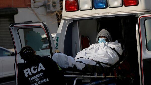 Un hombre en mascarilla y un médico durante el brote de coronavis en Nueva York, EEUU - Sputnik Mundo