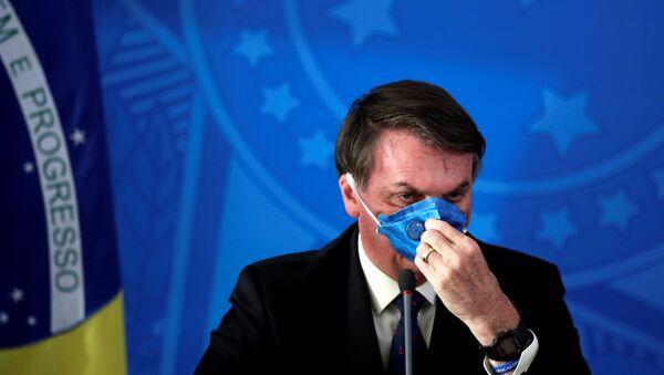 El presidente de Brasil Jair Bolsonaro acomodando una mascarilla - Sputnik Mundo
